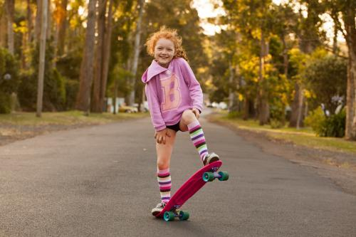 Girl smiling on a skateboard in the street