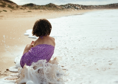 Girl splashing waves as they roll in
