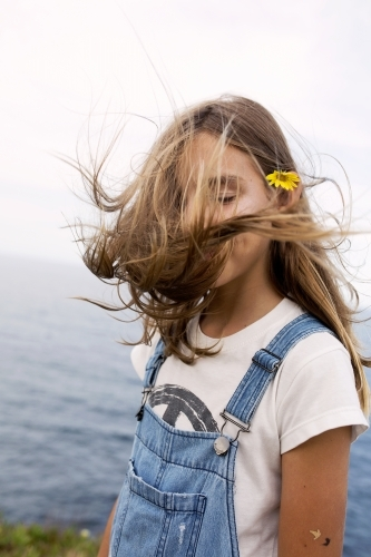 Girl standing by the ocean with hair flying in her face