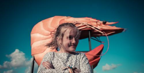Girl standing in front of a giant prawn