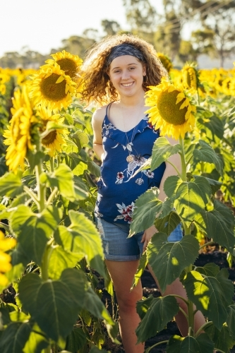 Girl standing in sunflower field