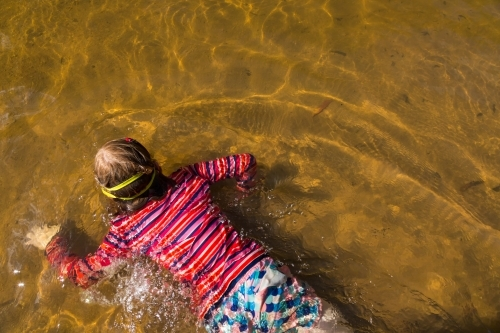 Girl swimming in a waterhole taken from above