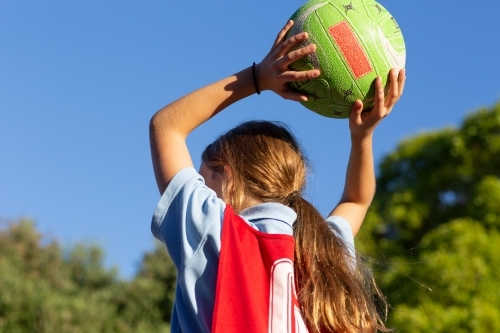 Girl throwing netball from behind