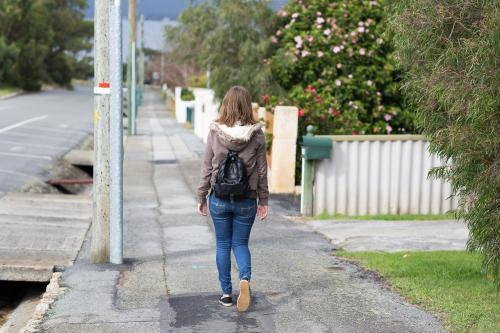 girl walking away along footpath