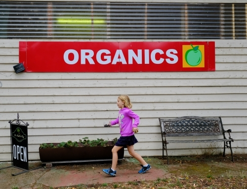 Girl walking past organic fruit farm shop