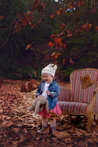 Girl With Hat Playing in Autumn Leaves