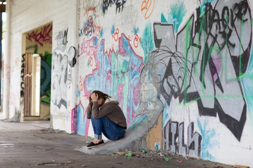 Girl with head in hands and wall of graffiti