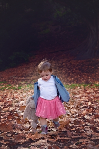 Girl With Toy Rabbit Running and Playing in Autumn Leaves