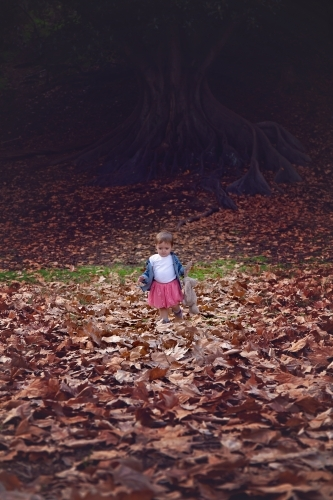 Girl With Toy Rabbit Walking in Autumn Leaves
