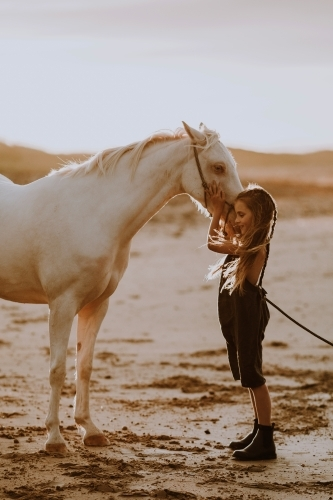 Girl with white horse on the beach at sunset