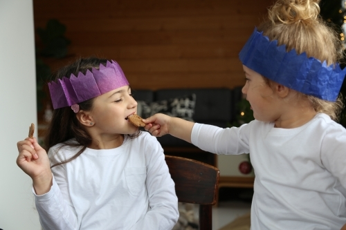 Girls in Christmas hats sharing gingerbread