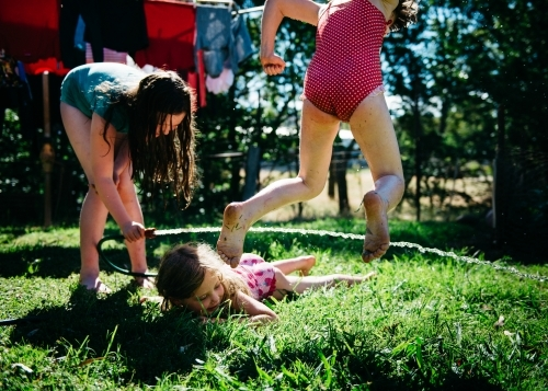 Girls playing under hose, jumping and crawling