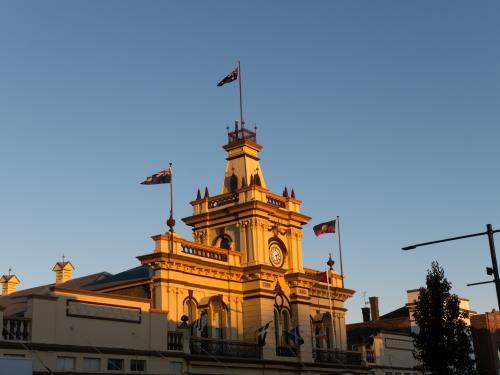 Glen Innes town hall in late afternoon sun and flags flying