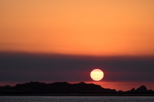 Glowing orange sunset with hazy sky over the rocky shore of the Kimberley coast Western Australia