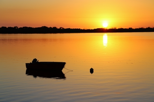 A calm golden sunrise over silhouetted dinghy on Pumicestone Passage