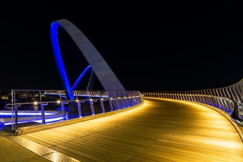 Golden lit path curving onto arched bridge with blue lighting and night sky