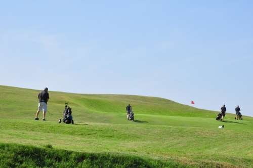 Golfers on green with blue sky