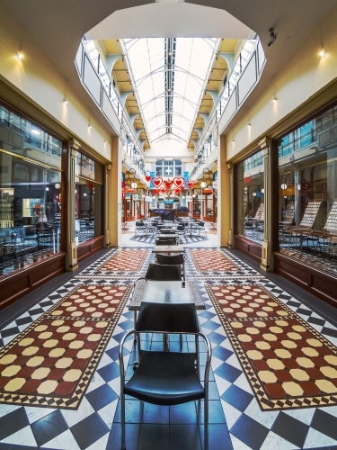 Interior of a shopping arcade with chairs and tables and decorative tile floor