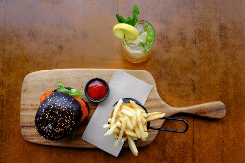 Gourmet burger in black brioche bun served with chips on a platter at a trendy cafe