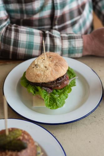 gourmet hamburger, indoors with man in checked shirt at table