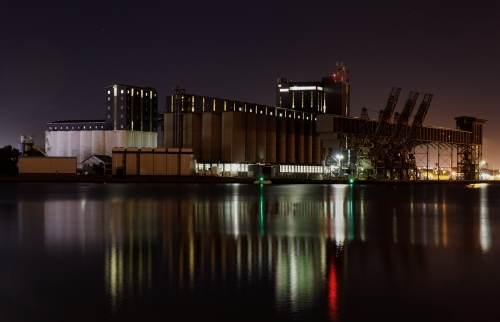 Carrington silos at night with lights reflected in water