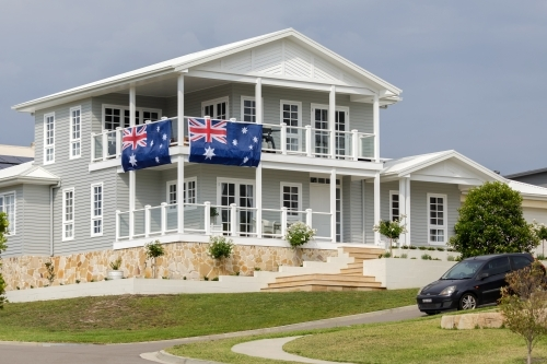 Grey and white Hamptons style house with two large Australian flags hanging from railings