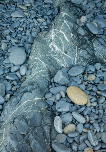 Grey-blue rounded waterworn rocks on the shore