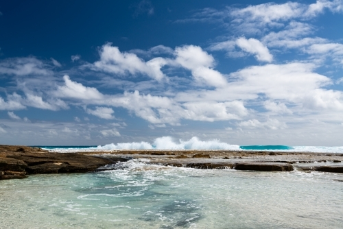 Ground level view of water flowing into rockpool with waves behind and dramatic blue cloudy sky