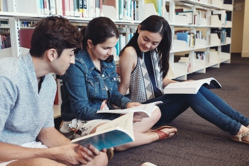 Group of international students reading in university library