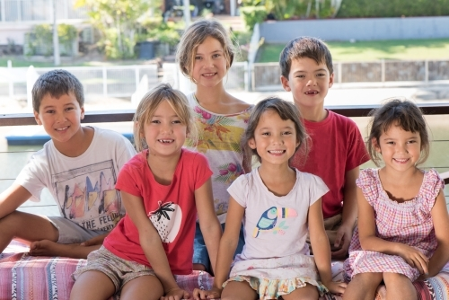 Group of six diverse culture Australian children smiling at camera while close together.