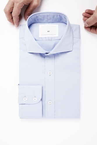 Hands styling blue tailored shirt on white background