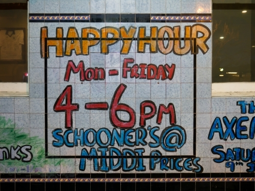 "Handwritten ""Happy Hour"" sign on tiles outside a pub"