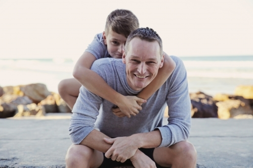 Happy father and teen son on the beach