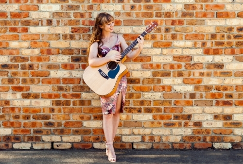 Happy female musician with guitar against brick wall