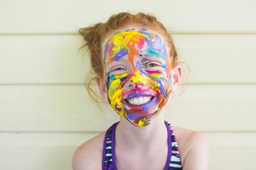 Happy girl with brightly coloured face paint