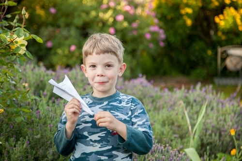 Happy kid making and flying paper planes in the garden