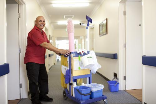 Happy male nursing home cleaner doing rounds