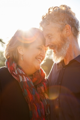 Happy middle aged couple together with sun flare close up