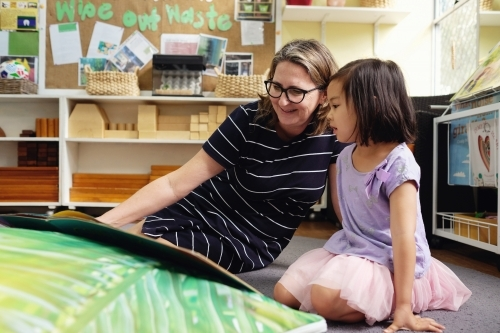 Happy multicultural teacher and child reading a book in kindergarten