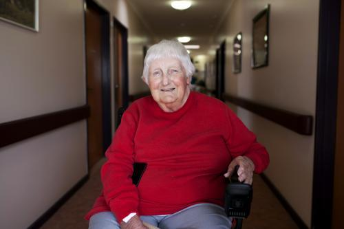 Happy nursing home resident sitting in wheelchair