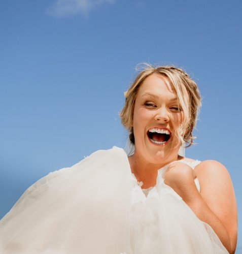 Happy smiling bride against a blue sky.