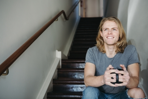 Happy smiling guy sitting on stairs with a coffee mug