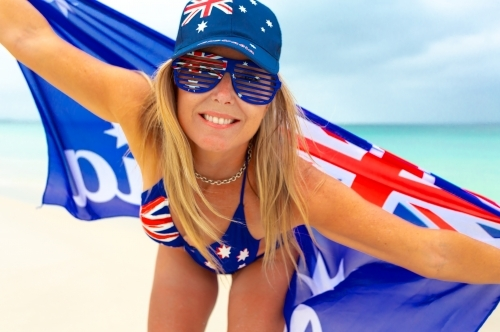 Happy smiling woman wearing Australian flag printed summer items, hat, sunglasses, and bikini
