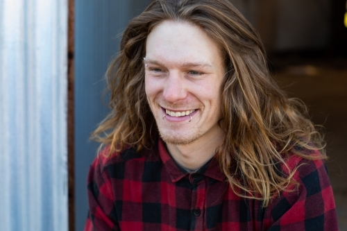 Happy smiling young man with long hair and lip piercings