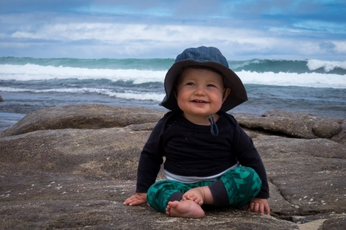 Happy toddler sitting on rocky beach with waves in background