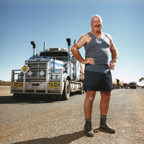 Happy truck driver standing front of road train