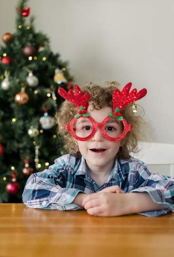 Happy young boy wearing novelty Christmas glasses