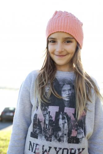 Happy young girl wearing beanie smiling at camera