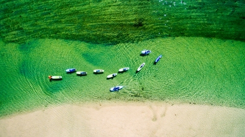 Ten paddle boarders on Cudgera Creek at Hastings Point from above