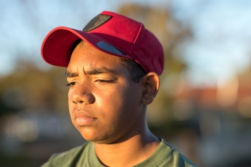 head and shoulders of surly looking teenager wearing cap